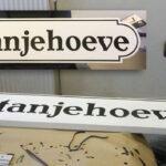 Voor aan de boerderij een naambord met de hand geschilderd