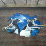 Muurschildering koeien die op de klaroen spelen op een muur bij de basisschool de Klaroen in Tienhoven